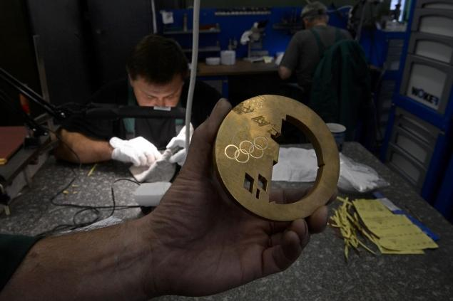A craftsman works a bronze medal for the 2014 Sochi Olympic Winter Games.