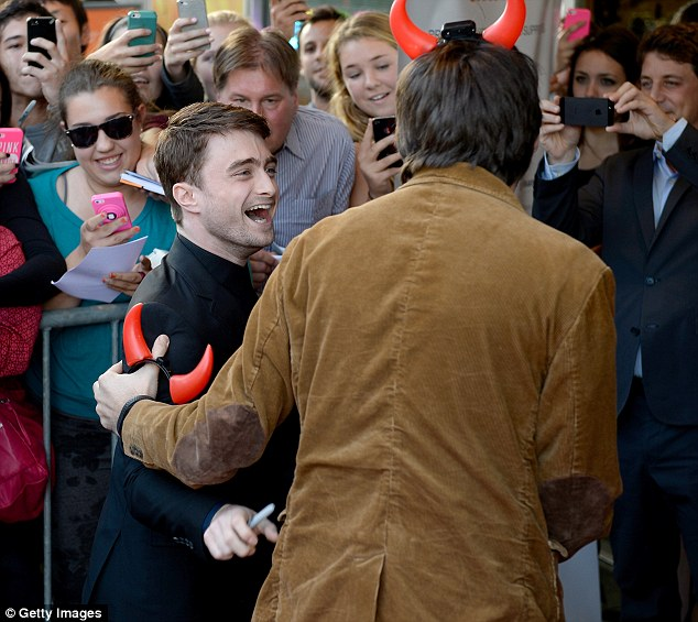 Daniel enjoys a joke with a costar, who dons red devil horns for the red carpet