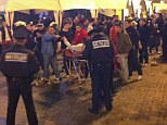 Hospitalised: An injured English fan lying on a stretcher and surrounded by medical personnel after the attack