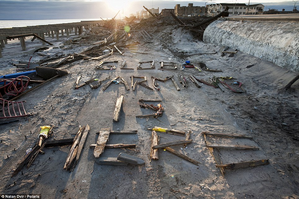 Powerful message: Wooden scrap from what used to be the Rockaway boardwalk is laid on the ground spelling 'Global Warming is Here.' The famous boardwalk was totally destroyed by the storm