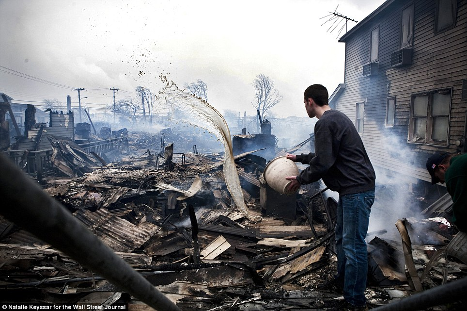 Joint effort: Some of the images on display include the works of professionals, like this photo taken October 30, 2012, depicting neighbors trying to extinguish the remnants of the fire which swept through the community of Breezy Point