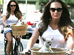 Tamara Ecclestone bicycles with her pet dog in the front basket.