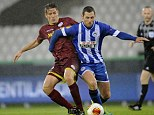 Battle: Wigan's Chris McCann tussles with Olafur Skulason at a wet Breydel Stadium