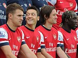 New boy: Mesut Ozil looked like hen was enjoying himself as Arsenal lined up for their official squad photograph for the season... but Jack Wilshere (left) didn't seem quite as happy