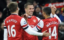 Arsenal's Theo Walcott (R) celebrates with teammates Aaron Ramsey (L) and Lukas Podolski (C) after scoring against West Ham