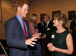 Careful there Harry! Prince Harry makes a suspect gesture as he chats to chief executive Liz Hughes (right) at a reception for MapAction at the Royal Society, London