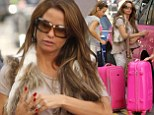 Business as usual: Katie Price jets out of UK for work in flurry of pink just days after hospitalisation