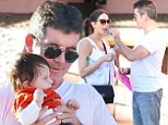 Practicing for fatherhood? Simon Cowell cradles a stranger's baby and hand-feeds pregnant girlfriend Lauren Silverman on romantic beachside date