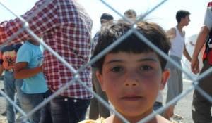 طفلة سورية تقف خلف الأسلاك الشائكة التي تحيط بمخيمات اللاجئين السوريين على الحدود السورية- التركية، 18 يونيو 2011. آلاف المواطنين السوريين يفرون إلى تركيا، هرباً من أحداث العنف التي تشهدها بلادهم. دخل تركيا نحو 8 آلاف مواطن سوري، بينما ينتظر على الحدود أكثر من 10 آلاف أخرين.