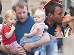 Guy Ritchie snatches a quick kiss from fiancée Jacqui Ainsley while on a stroll with their two adorable kids