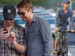 Here's to never growing up! Gerard Butler engages in some outright peculiar tomfoolery with a giggling friend on the streets of NYC
