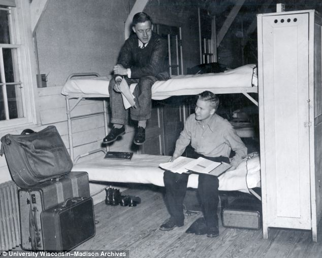 Two students pose on bunk-beds in their and appear to have just moved in as their luggage is not yet unpacked