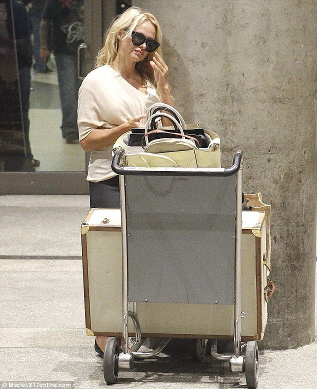 In charge of herself: The star even had to cart her own luggage outside of the airport