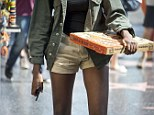 A young woman carrying a pizza walks down Hollywood Boulevard in Hollywood, California, on September 17, 2013
