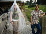 White power wedding: 'Little Charlie' shows off her custom made Klan wedding veil as her fiancé watches on. These photographs show the little-seen rituals and home lives of the far right organisation