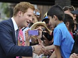 Good to meet you! Prince Harry shakes hands with a small boy during his first official tour of the country