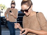 Make-up free Lauren Conrad jets out of LAX in casual top-bun, fuzzy jumper, and skinny jeans