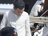 Harry Styles looks weary as he boards a private jet in Sydney bound for New Zealand