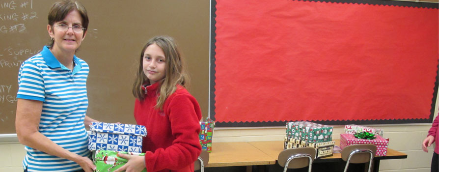 Mrs. Bruchac and Ashley Intile prepare shoeboxes of school supplies for children in Orange.