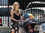 'Safety is my top concern': A $330 stroller designed by Heidi Klum for Babies 'R' Us has been deemed 'unsafe' by testing experts - here the supermodel is seen using the buggy in New York this June