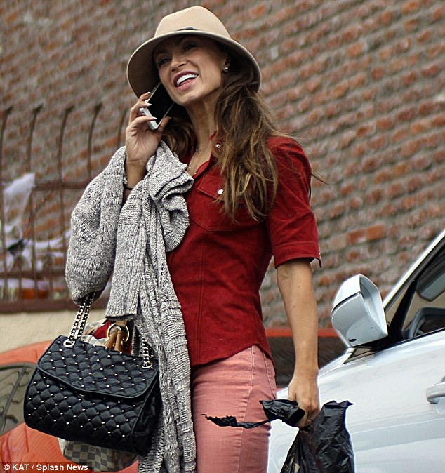 Ready for the rain: Karina Smirnoff arrived wearing a hat as she carried a grey cardigan to the dance studio