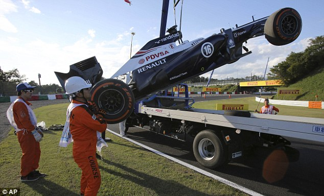 Recovery: Pastor Maldonado's Williams is carted back to the pit-lane after he crashed in the second practice session