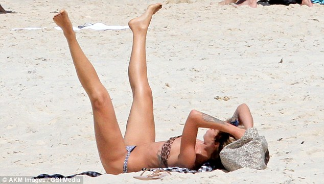 And one, and two...: The heiress did a few leg exercises on the sand while listening to music