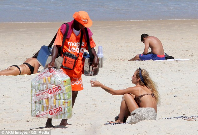 Quenching her thirst: Dellal buys a beverage from a local vendor to beat the heat