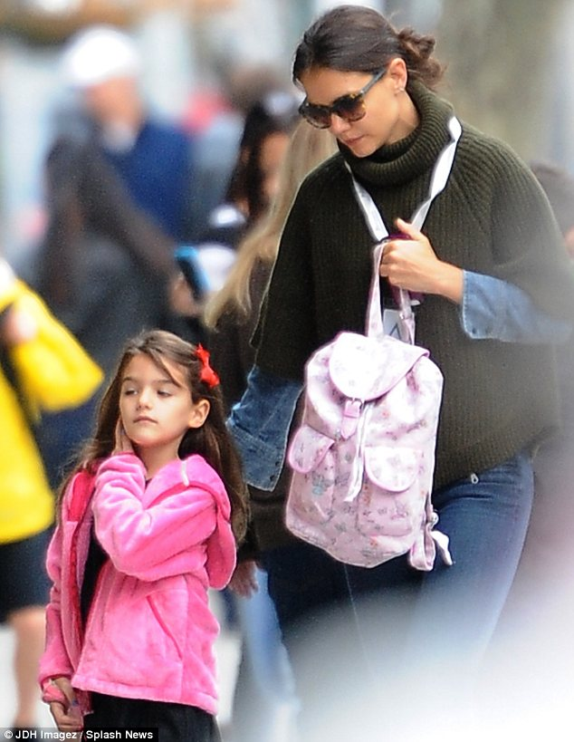 Doting mother: The 34-year-old held on tight to her little girl and carried her pink printed rucksack