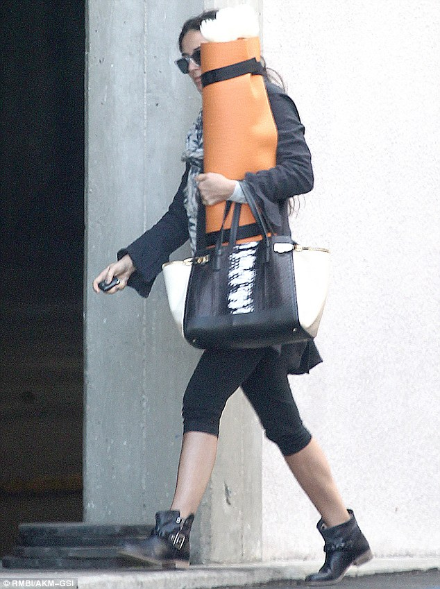 Why so shy? Demi Moore hid behind her orange yoga mat as she left a class in Hollywood, California on Thursday