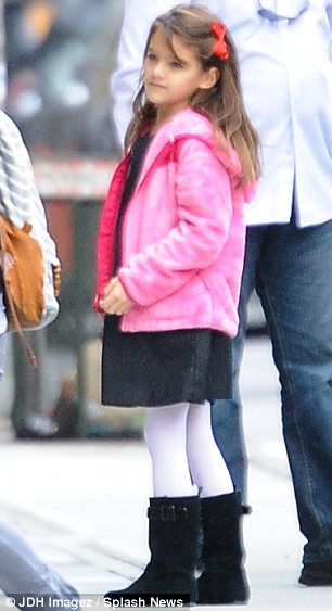 Mini fashionista: Suri looked cute in a black dress and boots, white tights, pink jacket and red bow in her hair