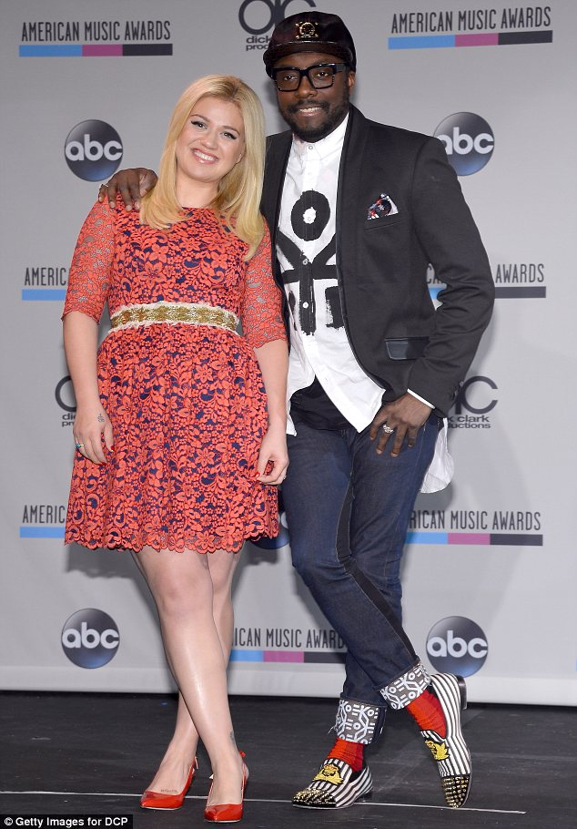 Dressed to impress: Kelly was glowing in a pretty red lace dress and matching red heels while will.i.am jazzed up his jeans, T-shirt and blazer combination with some interesting striped shoes and red socks