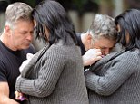 Alec Baldwin plants a tender kiss on baby Carmen while taking a stroll with his two leading ladies