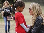 Buttercup's the boss! Heidi Klum can't get enough of her tiny new puppy as she supports daughters at soccer match
