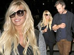Home sweet home! Jessica Simpson holds onto fiance Eric Johnson's arm as they return to Los Angeles after weekend away