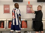 Seeing red: Youssouf Mulumbu poses with referee Dave Nixon in the Hawthorns toilets to raise awareness of the Be Clear on Cancer campaign