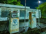 Abandoned gas station on the edge of Mineral Wells, Texas: It is dark with a 1/2 moon, ambient light of all kinds from several directions, CTO-gelled NEBO Redline flashlight and Noel uses a Mercury-vapor lamp behind the building to light up the trees