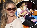 A skull-tastic slide! Rebecca Gayheart holds on tight to daughter Georgia as they take a riveting ride at the pumpkin patch