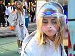 Cara Delevingne teams odd helmet with stylish grey outfit on DKNY set