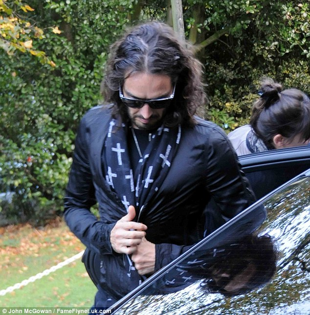 Man in black: Russell wore a cross print scarf as he got out of his car