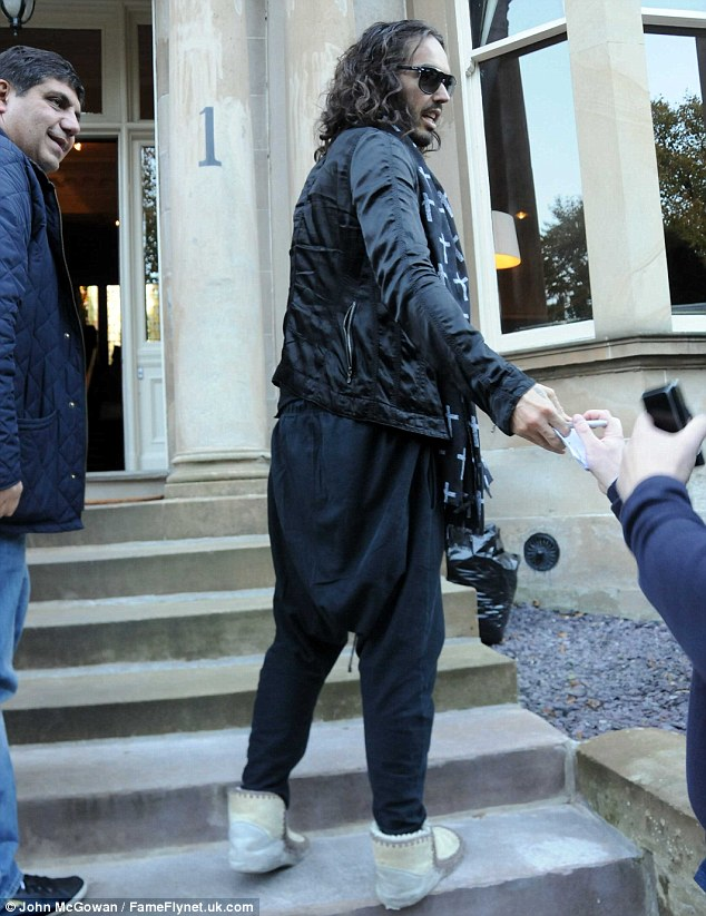 Odd: Russell looked to be wearing slippers and black harem-style trousers