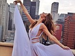 Simply angelic! Gisele Bundchen snares the attention away from the stunning New York skyline as she does a balletic-style pose in a lavender cut-out gown