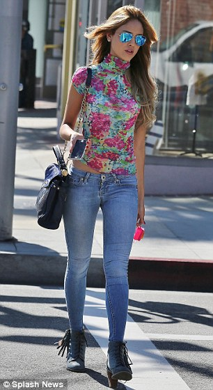 Summery: Eiza sported blue accessories in the form of a handbag, boots and mirrored aviator sunglasses