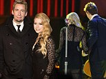 Avril Lavigne cuts a racy figure in black lace dress as she performs with husband Chad Kroeger at charity concert