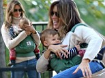 Supermom! Gisele Bundchen whizzes down a slide with Vivian while carrying her in a sling during fun-filled family day at the park
