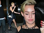 Wardrobe change: Miley Cyrus looked cute and casual in a black playsuit dressing it down with a blue and black plaid shirt tied around her hips