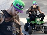 Zayn Malik rides tiny green quad bike while sporting a rock band vest during some downtime in Sydney