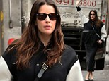 Game on! Liv Tyler hails a cab in over-sized varsity sports jacket and leather pencil skirt