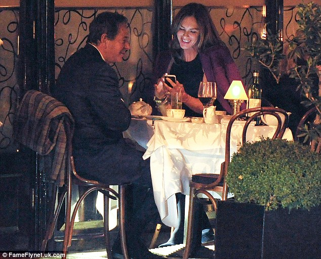 What's so funny? Saatchi and Trinny shared a joke after she showed him something on her mobile phone