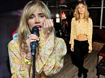 Suki Waterhouse shows off toned tum in cropped floral blouse as she performs at magazine launch after guitarist takes three attempts to begin